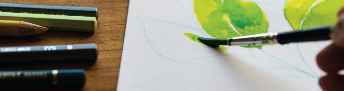 watercolor paintbrush filling in a lime green leaf on a white piece of paper